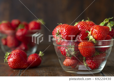 Ripe red strawberries on wooden table 69228430