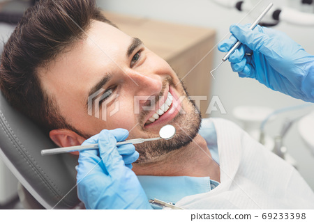 Man having teeth examined at dentists 69233398