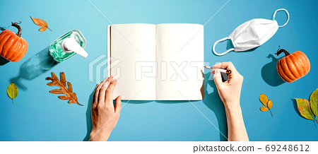 Notebook with a mask and a sanitizer bottle 69248612