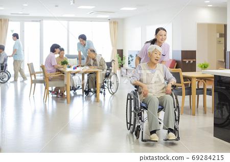 휠체어를 타고 시니어 여자와 간병인 노인 홈 69284215