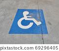 Blue sign on the asphalt about disabled parking 69296405