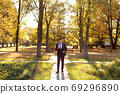 Young successful businessman eating ice cream walking in the autumn Park. 69296890