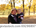 Portrait of grandmother with a charming little grandson in the autumn Sunny Park 69296897
