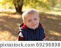 Portrait of a cute little boy in a vest in the autumn Park on a bench. 69296898