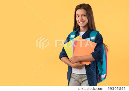 Smiling girl holding textbooks at studio background 69305845