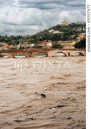 Ponte Pietra - Stone bridge and Adige river in flood in Verona Italy 69307471