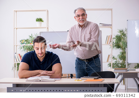 Old teacher and young male student in the classroom 69311342