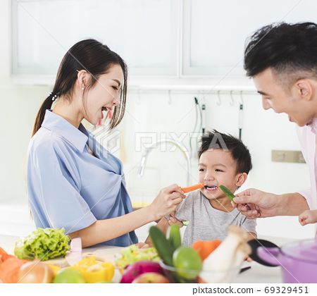 parent feeding boy a piece of  carrot in kitchen 69329451