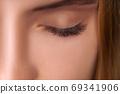 Eyelash Extension Procedure. Woman Eye with Long Eyelashes. Close up, selective focus. 69341906