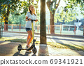 Smiling woman rides electric scooter or e-scooter in city park at sunset. Female using electric transport in urban park 69341921