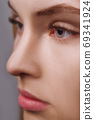 Eyelash Extension Procedure. Woman Eye with Long Eyelashes. Close up, selective focus. 69341924