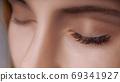 Eyelash Extension Procedure. Woman Eye with Long Eyelashes. Close up, selective focus. 69341927