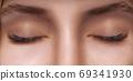 Eyelash Extension Procedure. Woman Eye with Long Eyelashes. Close up, selective focus. 69341930