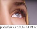 Eyelash Extension Procedure. Woman Eye with Long Eyelashes. Close up, selective focus. 69341932