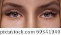 Eyelash Extension Procedure. Woman Eye with Long Eyelashes. Close up, selective focus. 69341940