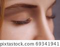 Eyelash Extension Procedure. Woman Eye with Long Eyelashes. Close up, selective focus. 69341941