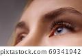 Eyelash Extension Procedure. Woman Eye with Long Eyelashes. Close up, selective focus. 69341942