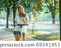 Smiling woman rides electric scooter or e-scooter in city park at sunset. Female using electric transport in urban park 69341951