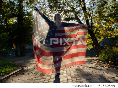 girl holding a fabric with a print of the American flag 69380349