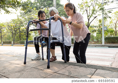 Asian mother and daughter help,care,support outdoor senior grandmother after cross the road,barrier from footpath,sidewalk is tall,different level area,elderly with walker,leg pain,lifestyle problem 69389591