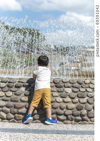 男孩碰噴泉的水 69391042