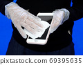 Coronavirus prevention cleaning, A young woman disinfects her smartphone with wet wipes and disinfectant. 69395635