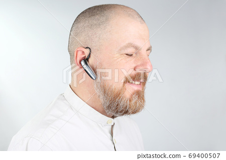 Bearded man in a light shirt with a Bluetooth in his ear. 69400507