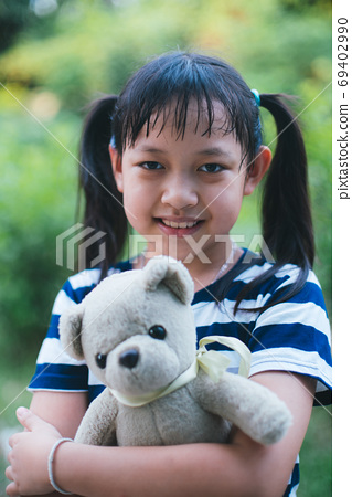 Smile little child girl hugging teddy bear with love 69402990