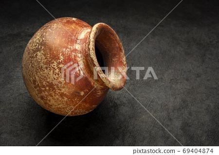 red clay pot on dark textured background 69404874