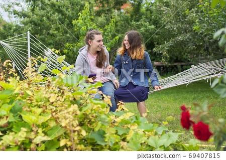 Two teenage girls having fun laughing on hammock in garden 69407815