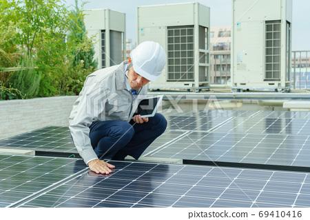 태양 전지 패널을 검사하는 남성 근로자 69410416