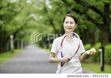 站立與網球拍的資深婦女 69418159