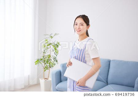 거실에서 PC를 가진 앞치마 차림의 젊은 여성 69419736