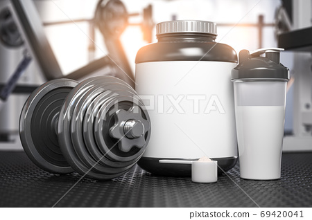 Whey protein can with dumbbell and shaker on the floor of gym. M 69420041