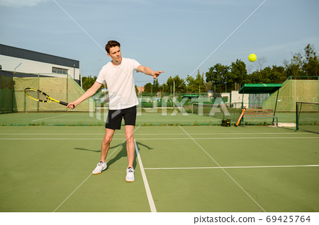 Male tennis player with racket hits the ball 69425764