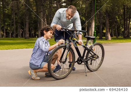 Closeup portrait of cheerful dad and son fixing bike 69426410