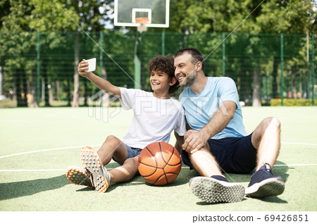 Happy dad and son taking selfie using smart phone 69426851