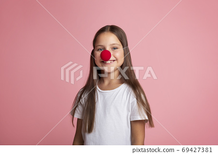 Celebrate birthday. Small girl in white t-shirt and red clown nose 69427381
