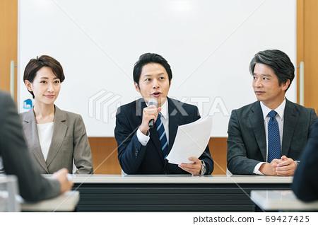 一個男人在新聞發布會上講話 69427425