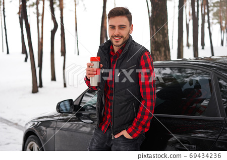Man in winter forest 69434236