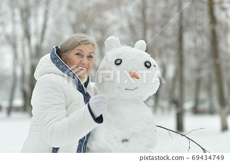 Happy beautiful senior woman posing in snowy winter park with snowman 69434749