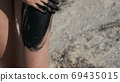 Healing black medical mud applies to leg and knee woman at the lake of salt water. Salty black dirt for people with health and skin problems. Relax at spa resort. Exfoliation scrub beauty treatment 69435015