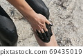 Healing black medical mud applies to leg and knee woman at the lake of salt water. Salty black dirt for people with health and skin problems. Relax at spa resort. Exfoliation scrub beauty treatment 69435019