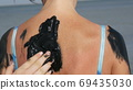Healing black medical mud applies on back woman at the lake of salt water. Salty black dirt Is good for people with health and skin problems. Relax at spa resort. Exfoliation scrub beauty treatment 69435030