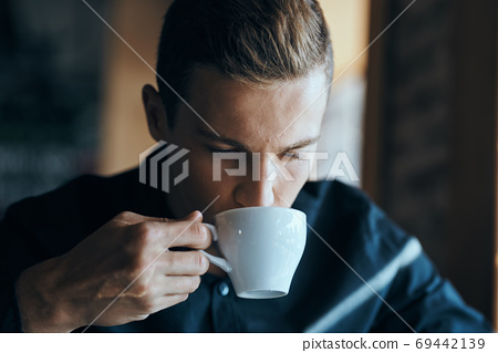 Businessman with a cup of coffee in a cafe and a dark shirt handsome face 69442139