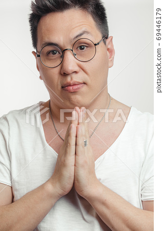 Asian man in t-shirt, holding hands in pray, begging for help or asking apology 69446179