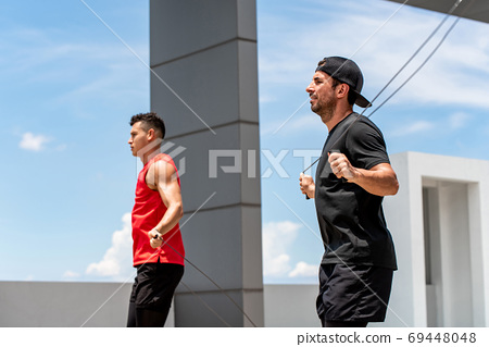 Two Caucasian sportsmen doing outdoor jumping rope exercise 69448048