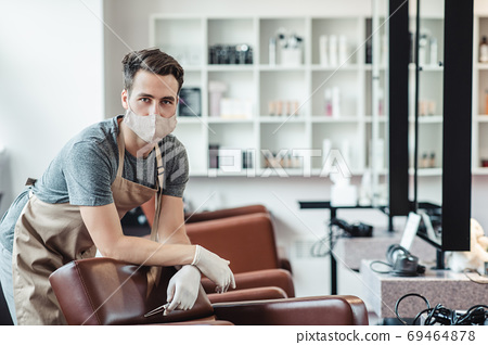 Male hairdresser in protective mask and gloves waiting for clients in empty salon interior 69464878