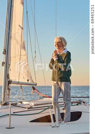 Enjoying amazing view. Vertical shot of a happy senior woman standing on the sailboat or yacht deck floating in sea at sunset, looking away and smiling 69465251