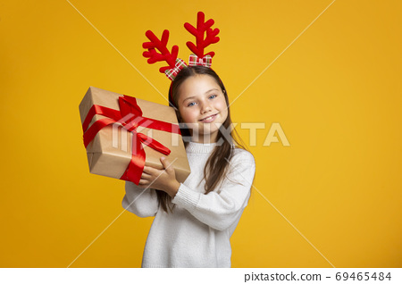 Gift from Santa Claus. Joyful girl holds present and listens to box 69465484